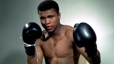 Muhammad Ali poses with his boxing gloves.
