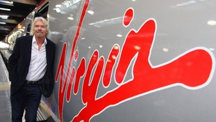 Richard Branson leaning against a Virgin Train.