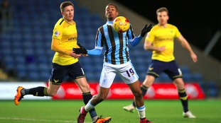 Mansfield Town's Reggie Lambe shields the ball from Oxford United's John Lundstram (left).