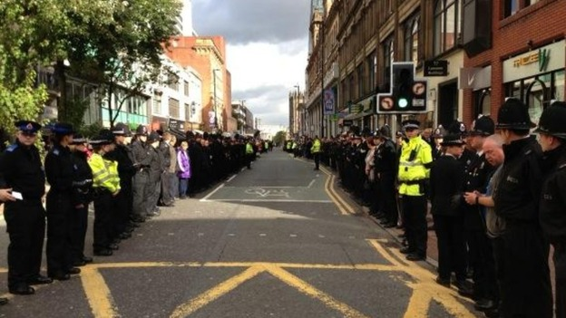Members of the public stand beside police officers in Deansgate Street in Manchester