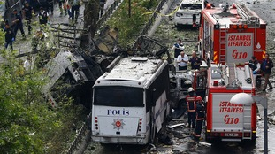 Fire engines stand beside a Turkish police bus which was targeted in a bomb attack in a central Istanbul district.