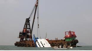 The sunken ferry is lifted out of the water off Hong Kong on October 2