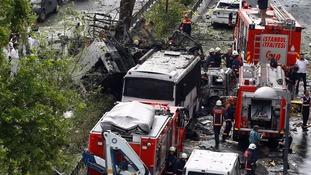 Forensic experts and firefighters stand beside a Turkish police bus targeted in an Istanbul bomb attack.