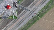 Helicopter shot of a person squatting next to the railway line