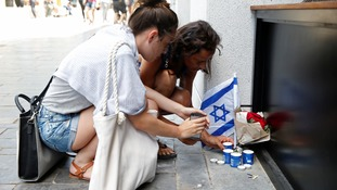Israelis light candles near the site of the shooting attack in Tel Aviv.