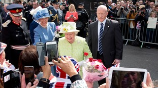 The greets the crowd lined outside Windsor Castle, Berkshire, along her walkabout to mark her 90th birthday.