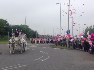 Horse drawn hearse on a roundabout as hundreds of people release pink balloons