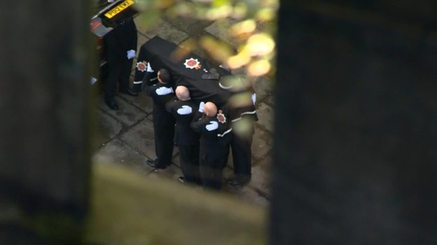 Officer carry the coffin following the funeral procession through Manchester