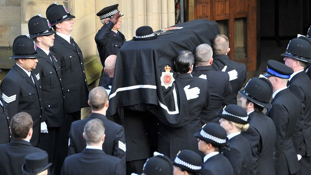 Greater Manchester Police Chief Constable, Sir Peter Fahy, salutes as the coffin is taken into Manchester Cathedral