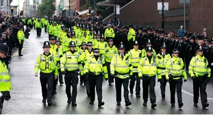 Police officers march along Deansgate