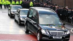 Roses rest on the bonnet of the hearse carrying the coffin