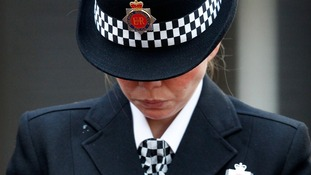 A police officer holds a single rose as she bows her head