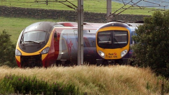 Virgin train passes a First Group train on the West Coast Main Line