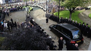 Line of police watch the funeral cortege of PC Fiona Bone