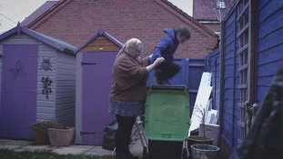boy jumps on rubbish in wheelie bin