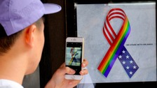 A man takes a picture of a rainbow solidarity ribbon ahead of a vigil in London's gay community.