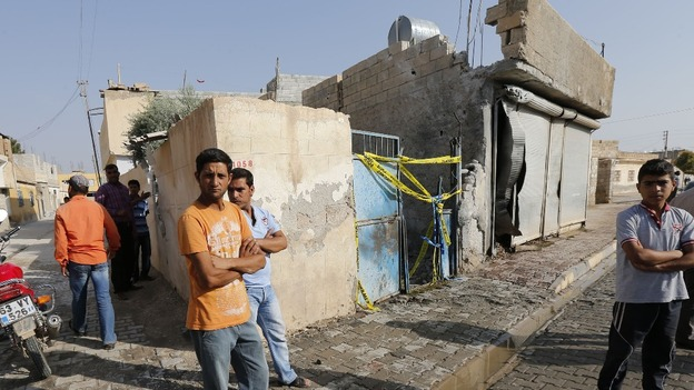 Men stand outside the house where five Turkish civilians were killed by a mortar bomb