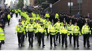 Police officers march along Deansgate as they make their way to Manchester Cathedral
