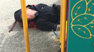 A man is out cold as drug pipe lies on the park next to a children's climbing frame