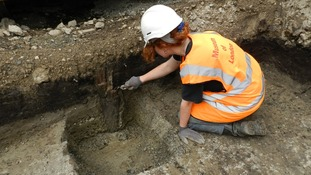 An archaeologist unearths a Bronze Age wooden stake.