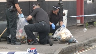 Officers empty bins as they look for evidence