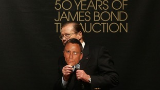 Sir Roger Moore holds a mask of current James Bond actor Daniel Craig at Christie's 50 Years of James Bond Sale.