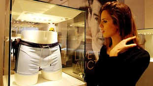 A member of the Christie's staff looks at the swimming trunks worn by Daniel Craig.