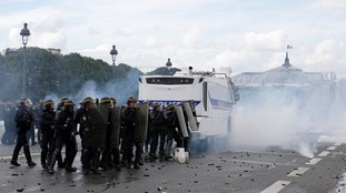 French CRS riot police stand next to a water canon vehicule during clashes with demonstrators at the Invalides square
