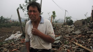A man stands on the debris of his house after the tornado struck