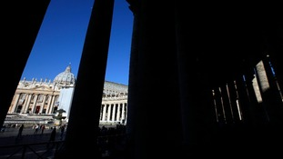 Saint Peter's Basilica is seen through the columnade at the Vatican