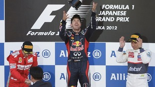Red Bull driver Sebastian Vettel of Germany, center, celebrates on the podium after winning the Japanese Formula One Grand Prix,