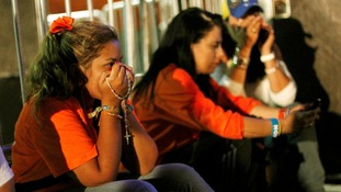 Crestfallen supporters of the opposition candidate Henrique Capriles
