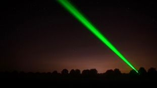 One of the laser lights cuts through the night sky