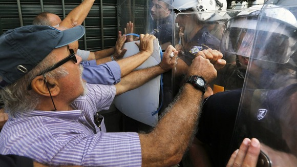 Pensioners push riot police during scuffles near the EU offices in Athens ahead of Merkel&#x27;s visit