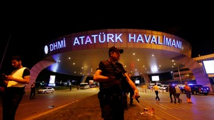 A riot police officer stands guard at the entrance of the Ataturk airport in Istanbul.