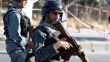 Afghan police stand guard after a suicide attack on a bus on Monday.
