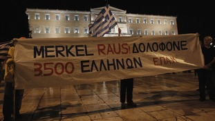 Protesters hold banner in front of parliament during rally against the upcoming visit by German Chancellor Merkel in Athens