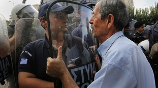A pensioner pushes a policeman in riot gear