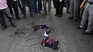 An EU flag is burned during a march towards the EU offices in central Athens