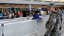 A US Army Specialist monitors the security line at John F Kennedy Airport on June 29 2016.