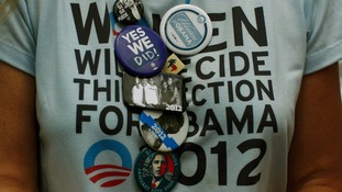 A supporter of President Obama wears a collection of badges during an election campaign rally in Colorado Springs