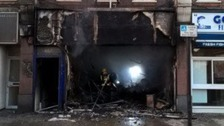 Car crashes into shop and bursts into flames