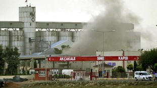 Smoke rises after a shell fired from Syria lands on the Turkish-Syrian border on October 7