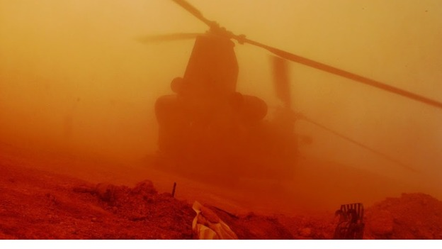 An RAF Chinook kicking up dust as it lands. 