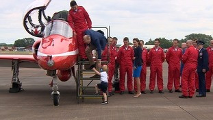 The Prince, wearing ear protectors, climbs up the steps to join his father at the Red Arrows Hawk.