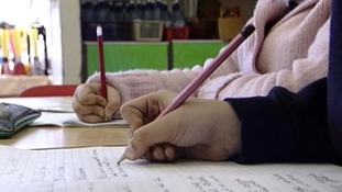 Children writing in a classroom.