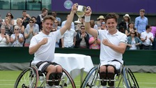 Alfie Hewett (left) and Gordon Reid (right) lift the trophy at Wimbledon.