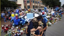Friends embrace next to tributes to the police officers killed in Dallas.