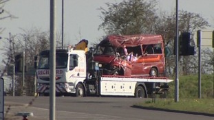 The crushed minibus getting towed away this morning