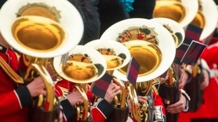 Troops are seen reflected in brass instruments